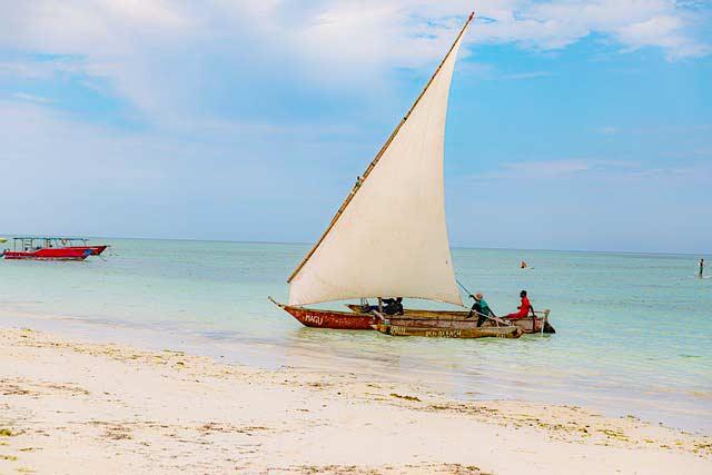 Einheimische im Boot vor Strand